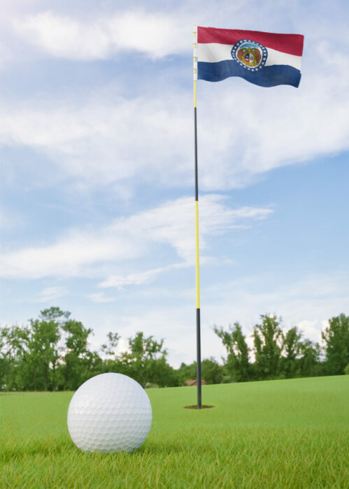 Missouri flag on golf course putting green with a ball near the hole